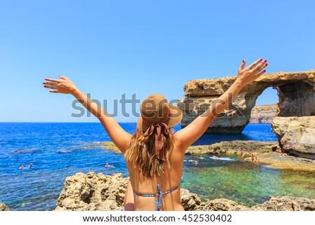 Back of female tourist wears hat, bikini, raises hands up and enjoys summertime with background of Azure window, famous tourist attraction on Gozo island, Mediterranean sea, Malta - stock photo