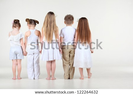 Back of four cute little girls and one boy in white clothes standing and holding hands. - stock photo