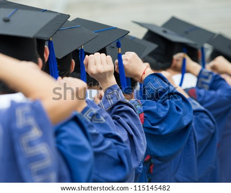 back of graduates put hands up during commencement.
