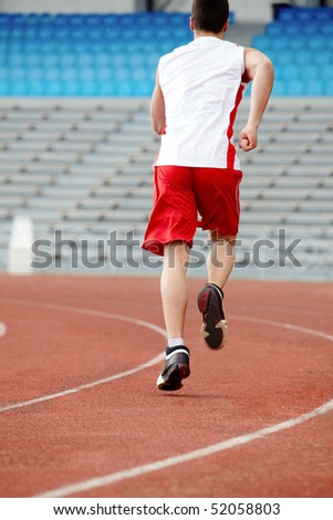 Back of guy in sportswear running down stadium track