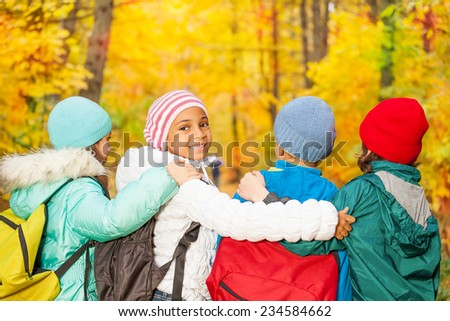 Back of kids with rucksacks standing in row close - stock photo