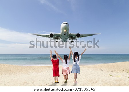Back of  little girls and one Boy  with  hands up on beach see Passenger airplane  landing , blue sky and sea background - stock photo