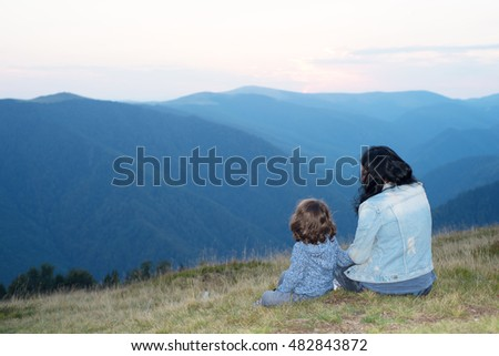 Back of mother and son sitting on grass in the mountains and having conversation