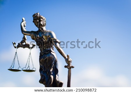 back of sculpture of themis, femida or justice goddess on bright blue sky background - stock photo