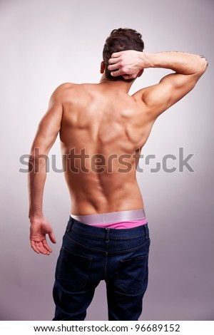 Back of sexy muscular man on gray background. back picture of a shirtless man in a fashion pose - stock photo