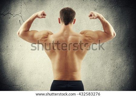 Back of sexy young athletic man who is showing muscles isolated on old cracked concrete wall background - stock photo