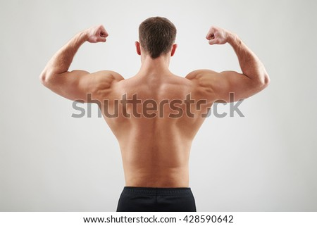 Back of sexy young athletic man who is showing muscles isolated on white background - stock photo