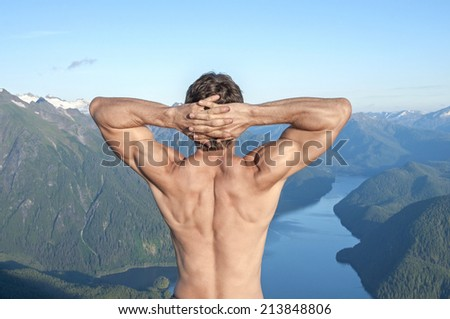 Back of shirtless muscular Caucasian man stretching arms with fingers behind head as he enjoys the magnificent scenic view over body of water surrounded by snow capped mountains near Sitka, Alaska - stock photo