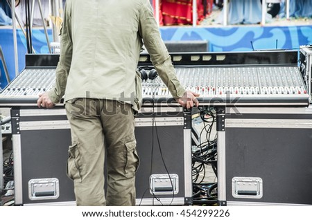 back of sound man stand against sound mixer control panel. headphones lie above. unrecognizable person.  - stock photo