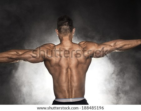 Back of strong muscular with hand extended - stock photo