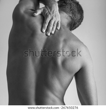 Back of Strong young Caucasian man with hand, black and white studio photo - stock photo