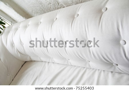 Back of white leather sofa. Textured button. Perspective of chesterfield sofa - stock photo