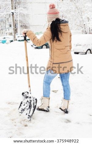 Back of woman take a break from shoveling snow in parking - stock photo