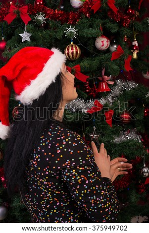 Back of woman wishing at Christmas tree in her home - stock photo