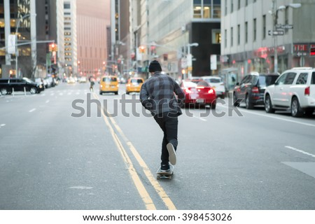 Back of young skateboarder cruise down the city street before sunset. Photographed in New York City in Feb 2016. - stock photo