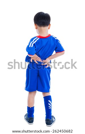 Back pain. Athlete little asian (thai) boy in blue sportswear standing and rubbing the muscles of his lower back, isolated on white background. Studio shot - stock photo