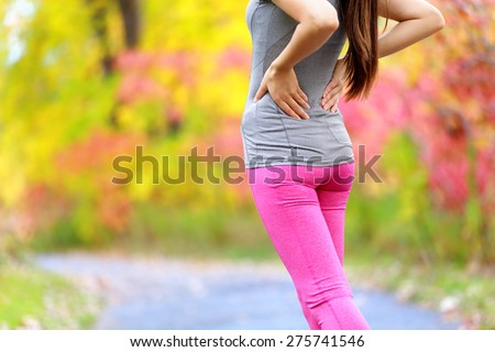 Back pain. Running woman with back injury in sportswear rubbing touching lower back muscles standing on trail path holding tired body outside in forest in fall. - stock photo