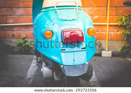 Back part of blue scooter in car park, vintage tone and retro style. - stock photo