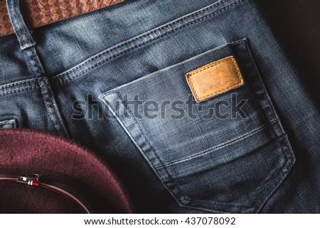 Back pocket of blue jeans with leather belt and fedora hat vintage color - stock photo