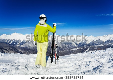 Back portrait of skier woman over mountains