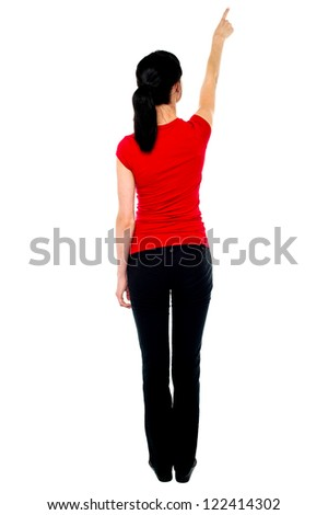 Back pose of woman in casuals pointing away isolated against white. - stock photo