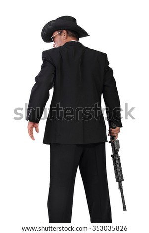 Back-shot of a western style hitman standing with gun in his hand, isolated on white background - stock photo