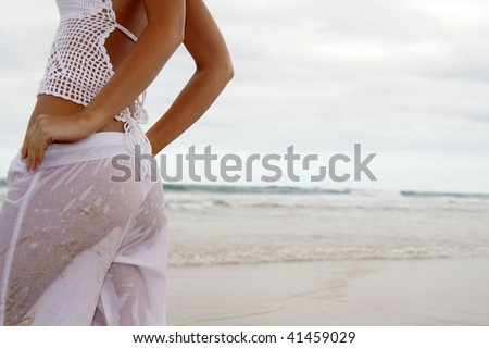 Back shot of beach beauty in wet white pants