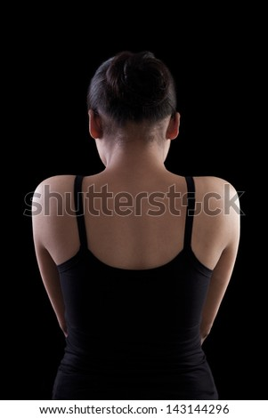 Back side of an asian woman in black dress on black background - stock photo