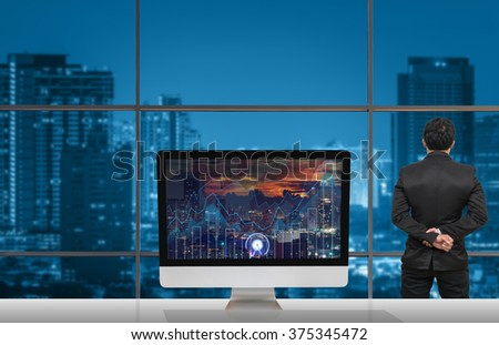 Back side of Businessman looking at city out off windows glass with Computer show Trading graph on the cityscape and world map background on the table in meeting room,Business financial concept - stock photo
