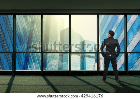 Back side of Businessman looking megalopolis through window, Business concept - stock photo