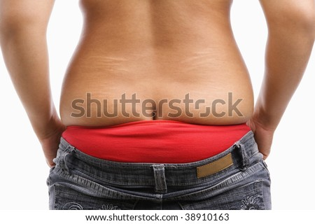 back side of fat woman trying to wear tight jeans, a concept for obesity issue - stock photo