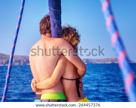 Back side of happy couple in love traveling on luxury sail boat along sea, romantic honeymoon vacation, summer travel and tourism  - stock photo