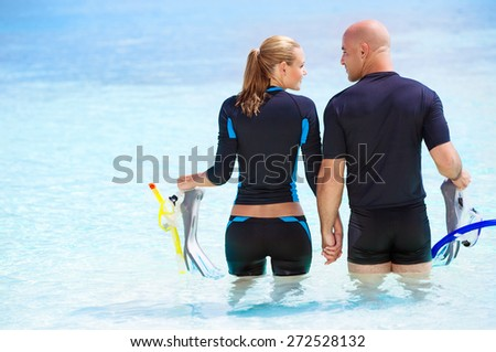Back side of happy diver couple standing in the water and preparing to dive, enjoying extreme sport and active summer vacation