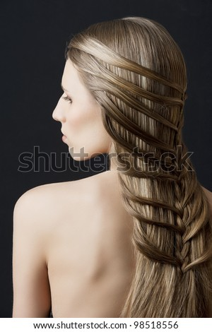 back side portrait of a fashion woman with long hair and old style and creative hairstylish, she is turned at her left and looks down - stock photo