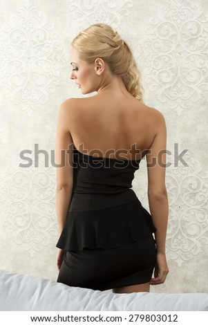back side shot of a young blond model , in elegant dress , looking on one side . she is in black - stock photo