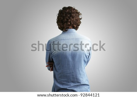 Back side view of a man against a grey background