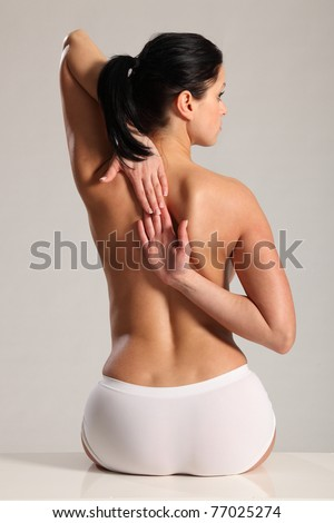 Back stretch and ache for beautiful young woman wearing white knickers with a naked back. - stock photo