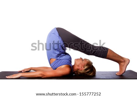 Back stretch Plow Halasana yoga pose by beautiful healthy woman with legs over her head, on white. - stock photo