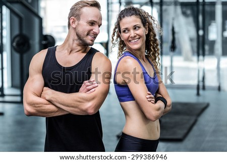 Back to back muscular couple looking at each other - stock photo