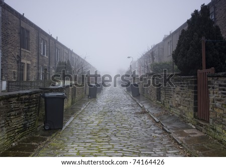 back to back terraced housing on cobbled street with bins out for collection - stock photo