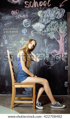 back to school after summer vacations, two teen girls in classroom with blackboard painted together - stock photo