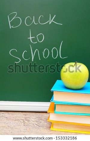 Back to school. An apple on books against a school board.
