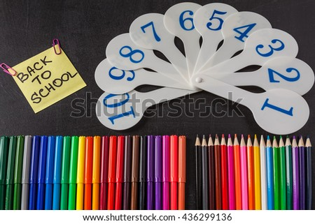 "Back to school background with a lot of colorful felt-tip pens and colorful pencils,  cards of numerals from one to ten and title ""Back to school"" written on the  piece of paper on the chalkboard - stock photo"