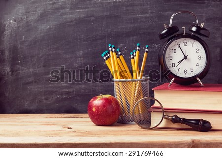 Back to school background with books and alarm clock over chalkboard - stock photo