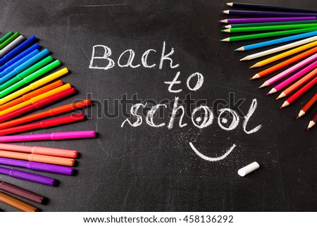 "Back to school background with colorful felt tip pens and title ""Back to school"" written by white chalk on the black school chalkboard - stock photo"
