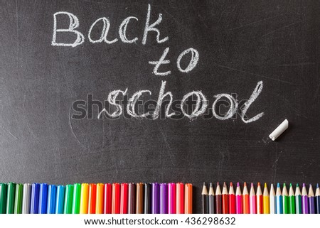 "Back to school background with colorful felt tip pens, pencils and the title ""Back to school"" written by white chalk on the black school chalkboard - stock photo"