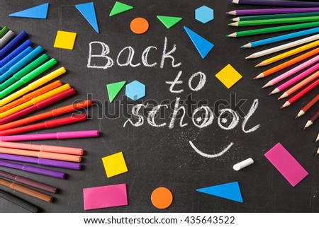"Back to school background with colorful felt tip pens, pencils,  title ""Back to school"" written by white chalk and colorful geometric figures on the black school chalkboard - stock photo"