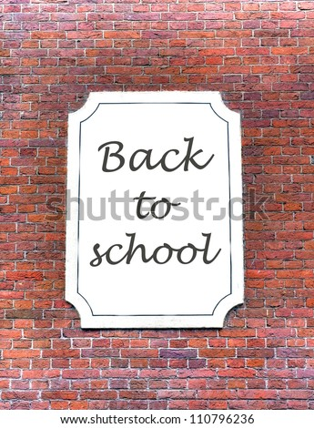 back to school banner on a white board hanging on a stone wall from school - stock photo