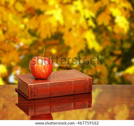 Back to school. Books and apple on the desk over autumn leaves