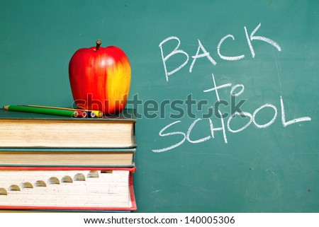 Back to School chalkboard and apple on books - stock photo